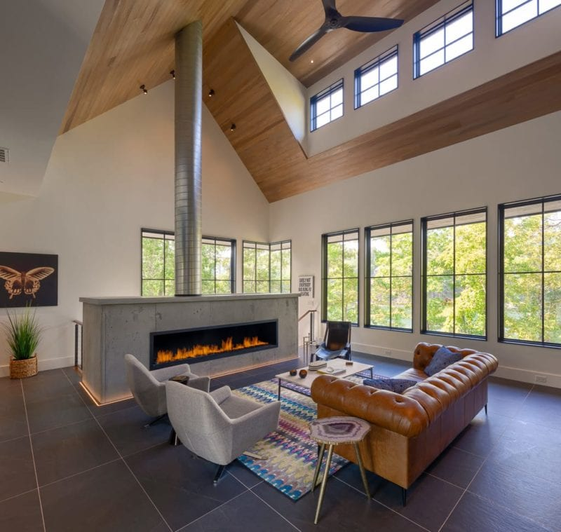Custom built home featuring living room with lit fireplace